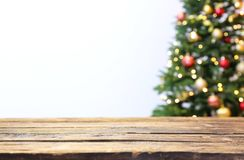 Wooden table and blurred Christmas tree with fairy lights stock image