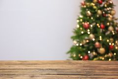 Wooden table and blurred Christmas tree. With fairy lights on background royalty free stock photography