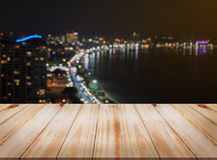 Wooden table with blurred night city skyline background Royalty Free Stock Photo