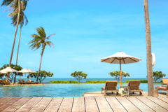 Wooden table with blurry tropical sea and resort background. Royalty Free Stock Image