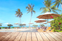 Wooden table with blurry tropical sea and resort background. Royalty Free Stock Photos
