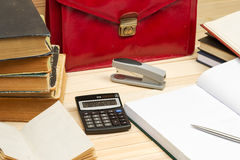 On a wooden table books, documents, calculator, red briefcase. Stock Photo