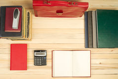 On a wooden table books, documents, calculator, red briefcase. Stock Image