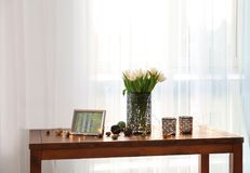 Wooden table with bouquet of tulips and decors. In living room Stock Photography