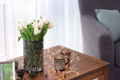 Wooden table with bouquet of tulips and decors. In living room Stock Photo