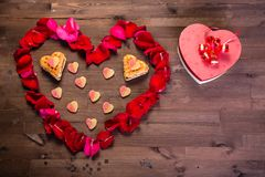 On the wooden table is a box in the form of a heart to the right of the heart of the rose petals Royalty Free Stock Photography