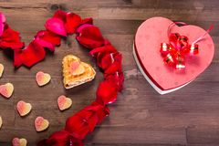 On the wooden table is a box in the form of a heart to the right of the heart of the rose petals Stock Image