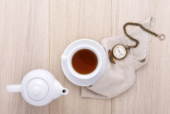 Wooden table for breakfast with cup of tea and watch and teapot Stock Photography