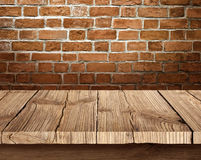Wooden table and brick background. Wooden table in front of the brick background photo Royalty Free Stock Image