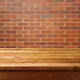 Wooden table and brick wall background Stock Photo