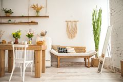 Wooden table in a bright rustic-style kitchen. Scandinavian style in the int stock photos