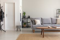 Wooden table on carpet in front of grey sofa in minimal living room interior with door. Real photo stock photography