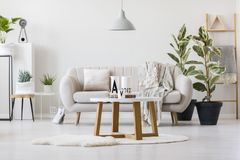 Wooden table in the center. Wooden table with decorative jugs standing in the center of living room interior with bright couch Royalty Free Stock Image