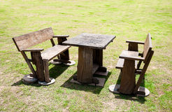 the wooden table and chair on green grass yard at noon time Stock Image