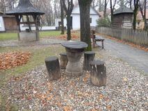 Wooden table and chairs in National Village Museum, Bucharest. Wooden table and chairs surrounded by fallen leaves in an autumn day, in the National Village royalty free stock photos