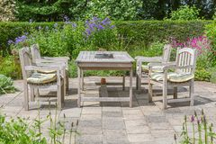 Wooden table and chairs in an ornamental garden Stock Photos
