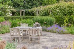 Wooden table and chairs in an ornamental garden Royalty Free Stock Image