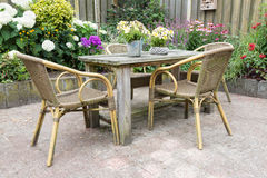 Wooden table and chairs in a ornamental garden Royalty Free Stock Photo