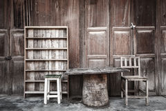 Wooden table,chairs,shelf in front of wooden house Royalty Free Stock Photos