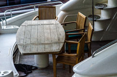 Wooden table and chairs at the stern of a large ship anchored in Royalty Free Stock Photo