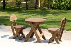 Table and wooden chairs in tropical garden next to the sea on the sand beach, Thailand. Close up Stock Photo