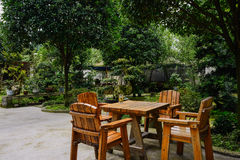 Wooden table and chairs in verdant yard on summer day Royalty Free Stock Image