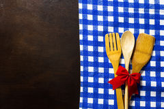 Wooden table with checked tablecloth and wooden kitchen utensils Stock Photo