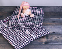 On wooden table checkered flannel pajamas and a sleeping soft Stock Images