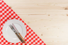 Wooden Table with Checkered Red Tablecloth Plate Fork and. Wooden Table with Checkered Red Tablecloth Plate and Cutlery Royalty Free Stock Photography