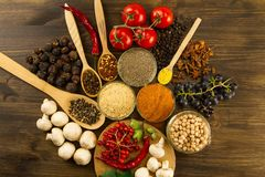 Wooden table with colorful spices, herbs and vegetables. Royalty Free Stock Photos