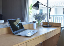 Wooden table with computer notebook,pencil,lamp and artificial flowers in modern working area at home Stock Photography