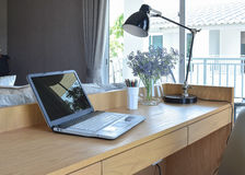 Wooden table with computer notebook,pencil,lamp and artificial flowers in modern working area at home Stock Photos