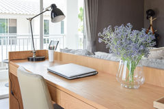 Wooden table with computer notebook,pencil,lamp and flowers in modern working area Royalty Free Stock Photography