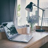 Wooden table with computer notebook,pencil,lamp and flowers in working area Royalty Free Stock Photos