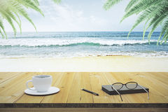Wooden table with cup of coffee, eyeglasses and diary on the bea Stock Photo