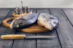 Wooden table cutting board with fresh raw dorado fish Royalty Free Stock Photo