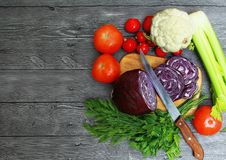 Top view on tomato, radish, greens, cauliflower, red cabbage, celery on a wooden table. On a wooden table on a cutting Board with a knife are tomatoes, radishes Royalty Free Stock Photos