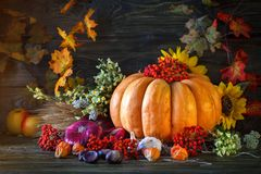 The wooden table decorated with vegetables, pumpkins and autumn leaves. Autumn background. Schastlivy von Thanksgiving