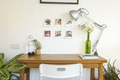 Wooden table and decorative elements in white room Royalty Free Stock Photography
