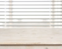 Wooden table on defocuced window with venetian blinds background Stock Photo