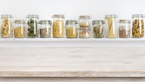 Wooden table on defocused background of groceries in glass jars.  royalty free stock photography