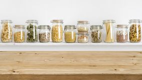 Wooden table on defocused background of groceries in glass jars stock photos