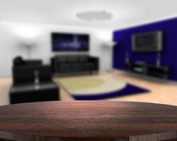 Wooden table with defocussed contemporary lounge Royalty Free Stock Images