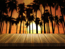 Wooden table with defocussed image of palm trees at sunset Royalty Free Stock Photos