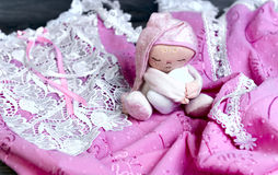 On a wooden table delicate pink nightgown. With lace and soft toy doll man sleep in a pink cap with a pillow in his hands Stock Photo