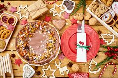 Wooden table with delicious Christmas cake decorations and different cookies. Old wooden table with delicious Christmas cake decorations and different cookies stock image