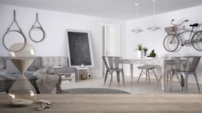Wooden table, desk or shelf with crystal modern hourglass measuring the passing time and house keys over modern scandinavian livin. G room, architecture interior stock photography