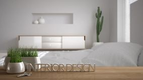 Wooden table, desk or shelf with potted grass plant, house keys and 3D letters making the words interior design, over blurred scan. Dinavian bedroom, project Stock Images