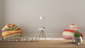 Wooden table, desk or shelf with potted grass plant, house keys and 3D letters making the words interior design, over blurred empt. Y room with armchairs Stock Photography