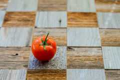 Wooden table from different wood mosaik textures, as chess board and fresh organic red ripe tomato with water drops Royalty Free Stock Photos